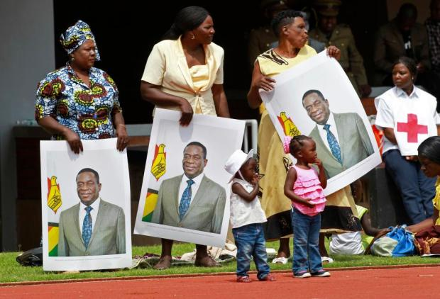 Supporters hold portrait of the newly sworn-in president in Harare.jpg