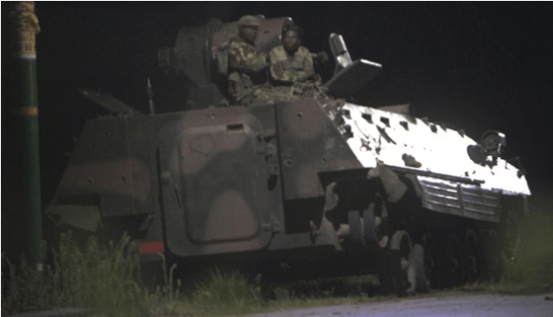 Two soldiers sitting in a tank on the outskirts of Harare where a suspected coup took place in the early hours of Wednesday morning