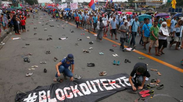 Protesters scatter pairs of slippers and shoes to symbolize victims killings in Duterte's so-called drug war.jpg