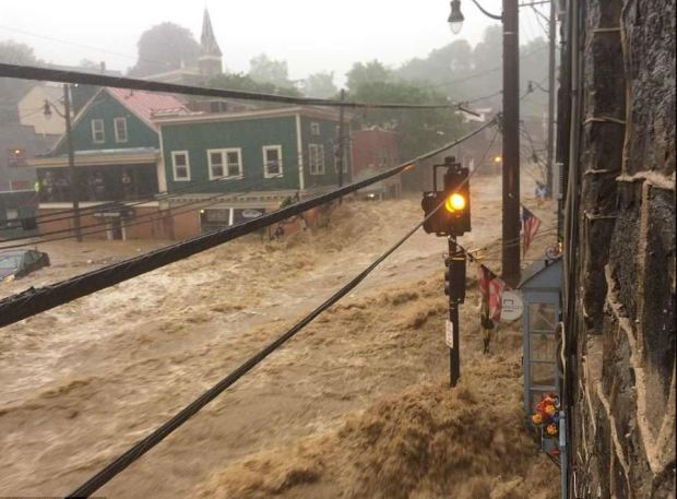Fast-moving torrents of brown water rushing down Main Street in Ellicott City, MD.JPG