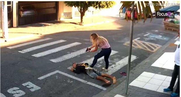 Officer Katia da Silva Sastre bends over a surprised  Elivelton Neves Moreira,after shooting him three times.JPG