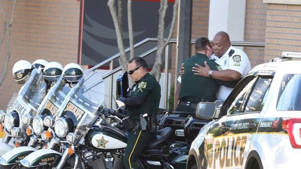 A Orange County Sheriff Motor deputy, center, gives support to a Orlando police motor officer, right, at Orlando Regional Medical Center after  a cop was shot and severely injured une 10, 2018.jpg