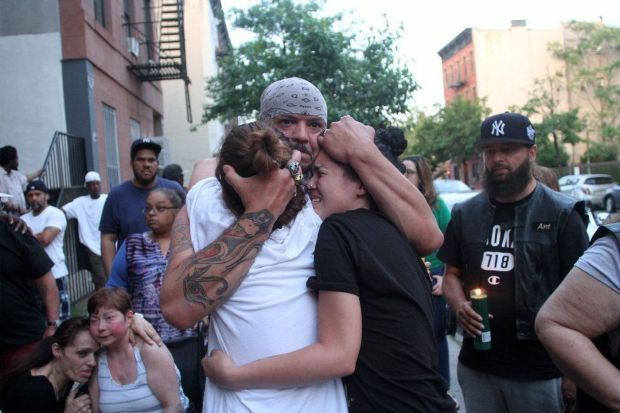 Mourners comfort one another at a candle light vigil for William Fernandez in Brooklyn.jpg