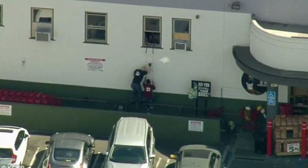 Police help hostages escape from a ladder near the front of the store