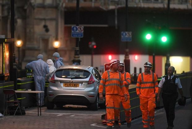 Forensic officers inspect the scene where the Ford Fiesta crashed near the Houses of Parliament.JPG