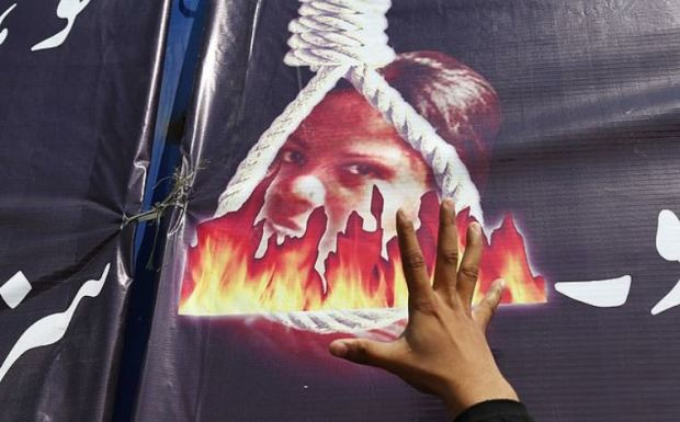 A poster carried at a protest in Karachi shows Asia Bibi's burning head in a noose.JPG