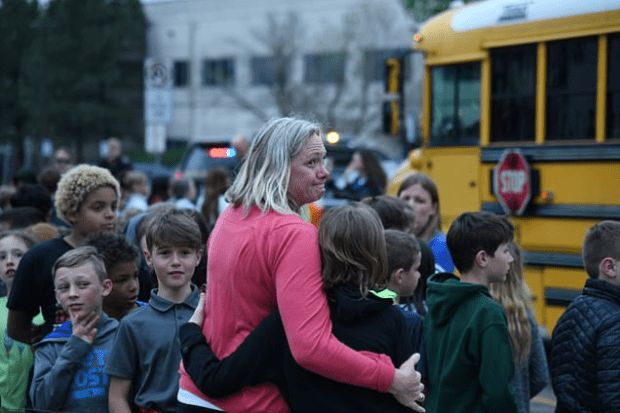Teacher embraces students in a parking lot near the STEM School Highlands Ranch in Colorado , after a shooter opened fire, injuring at least eight people on May