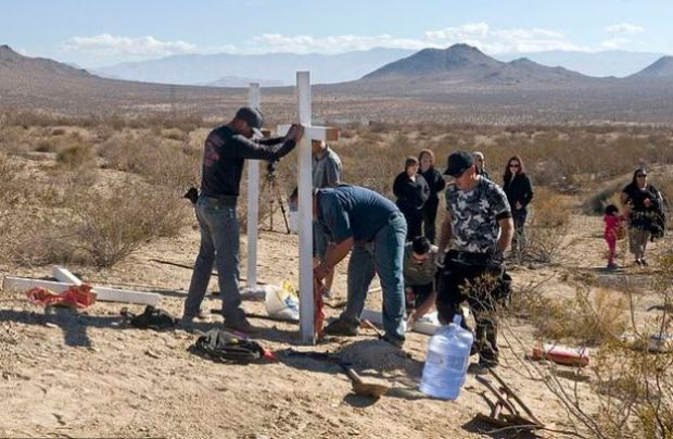 Mourners place crosses place crosses near the graves of the McStay family in Victorville, California, 1