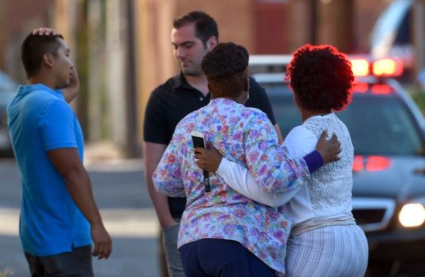 Two women embrace in an alley behind the Man Alive drug treatment center in Baltimore, MD 2