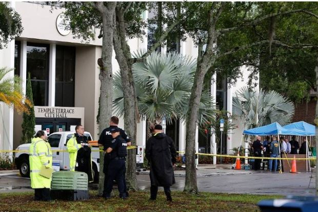Police mark the parking lot outside the Temple Terrace City Hall in Florida on Friday after the officer-involved shooting with Yellow evidence markers