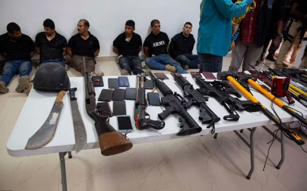 This image has an empty alt attribute; its file name is Weaponry-mobile-phones-passports-and-other-items-are-being-shown-to-the-media-along-with-suspects-in-the-assassination-of-president-Jovenel-Moise-4.jpg