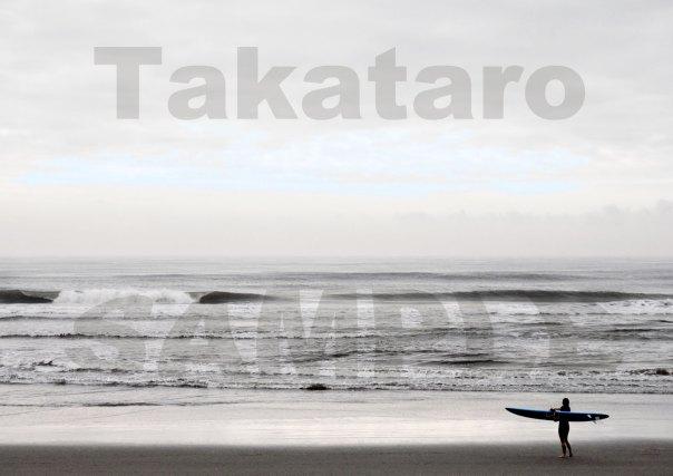 夏の終わりの早朝、海から上がってきたばかりの女性サーファーが、名残惜しそうに振り返って海を見つめていました。