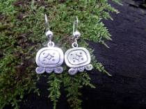 """Maya Nawal Glyph """" Q'anil """" Earrings $45.00 Amount Available: 1 This glyph represents the perforation of the earth during the planting of corn, creating a small hole in the soil to deposit the four seeds that represent the four colors of corn and the four races of humanity: red, black, white, yellow. Q'anil signifies germ; seed; life and creation. Creation of the universe, especially life and Mother Nature. It's a day to ask for life; the germination of the sacred Maize and everything else that Mother Nature produces."""