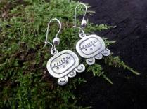 """Maya Nawal Glyph """" Ix """" Earrings $45.00 Amount Available: 1 The glyph signifies the heart of the planet, female reproduction, the face of a jaguar, the print of a jaguar, and the points of a map of the world. Ix signifies the jaguar and the tiger, female and feline energy. It represents the Mayan altar, the intelligence of mother earth; the seven guacamayas; a high level of developed consciousness; spirit protector of the planes and the mountains. Ix signifies the creative forces of the universe."""