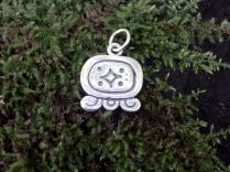 """Maya Nawal Glyph """" Q'anil """" Pendant $30.00 Amount Available: 1 This glyph represents the perforation of the earth during the planting of corn, creating a small hole in the soil to deposit the four seeds that represent the four colors of corn and the four races of humanity: red, black, white, yellow. Q'anil signifies germ; seed; life and creation. Creation of the universe, especially life and Mother Nature. It's a day to ask for life; the germination of the sacred Maize and everything else that Mother Nature produces."""