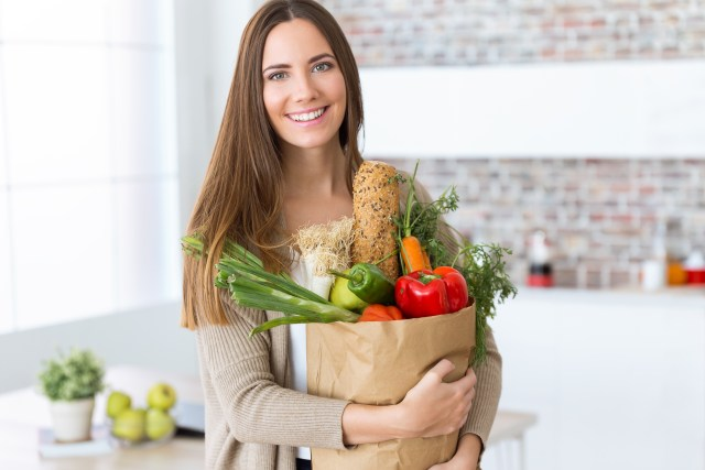 Happy And Healthy Woman Holding A Bag Of Groceries Fruit And Vegetables While Smiling