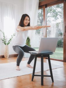 woman exercising online workout at home from laptop