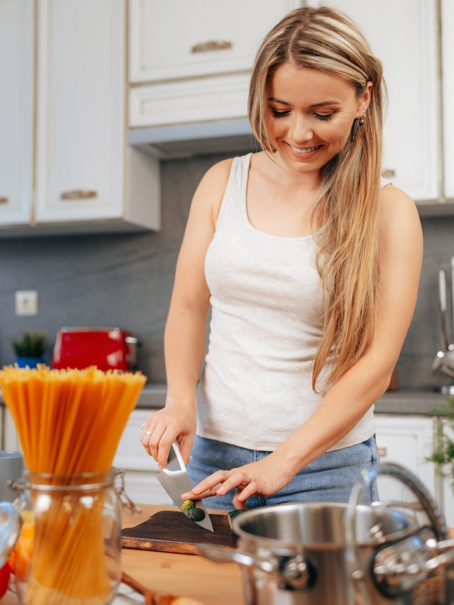 Smiling young woman cooking something at her kitchen