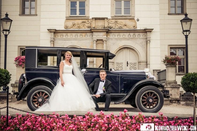 Pałac Wojanów w tle, a na pierwszym planie Jessi i Alex oraz ich kareta   Fotograf na ślub Konrad Żurawski