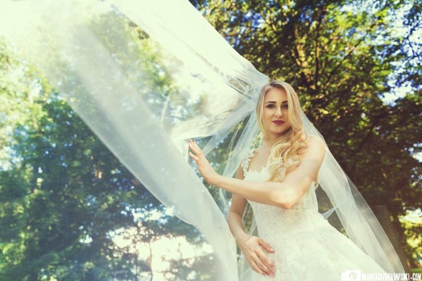 Ślubna sesja do dobry moment do wykorzystania ślubnych akcesoriów, np. welona | Fotograf Konrad Żurawski