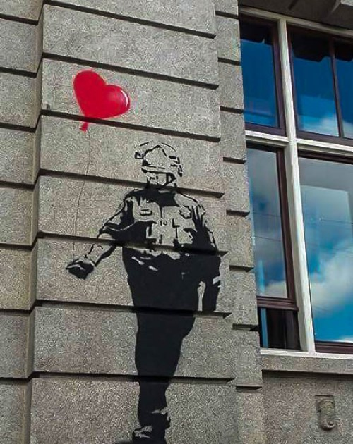Tyler Street Art of a soldier holdin a heart baloon in Prins Hendrikkade in Amsterdam Dutch capital