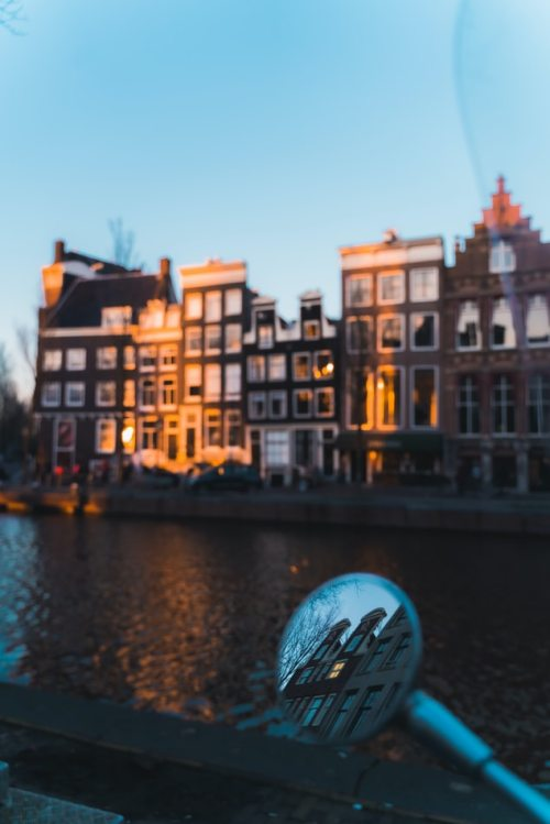 Amsterdan houses along the canals with reflection in the rearview of the scooter