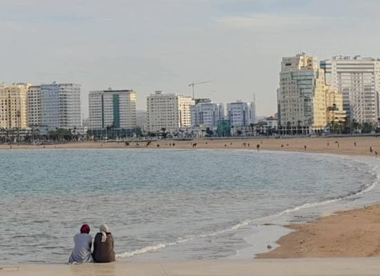 Beach view in Morocco with two women and a city in the background