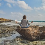 girl meditating on the rock surrounded by the beach