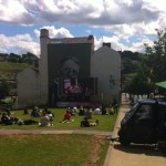 Take12trips: outdoor cinema screen and people watching movies on the grass in the sun