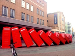 Kingston: traditional discarded telephone boxes displayed in a row, falling on top of each other, like a domino effect