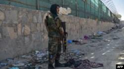 Seorang pejuang Taliban melakukan pengamanan di lokasi terjadinya serangan bom di luar bandara Kabul hari Kamis (26/8).