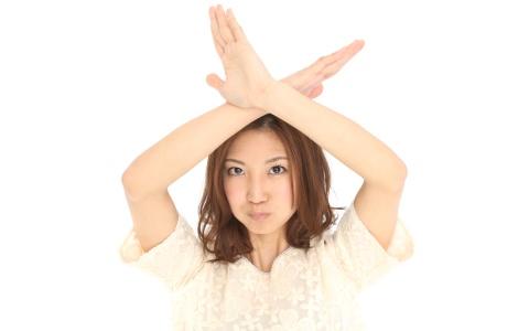 バツのポーズをする女性