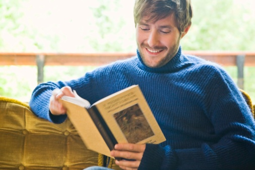 Man reading book and sitting on sofa