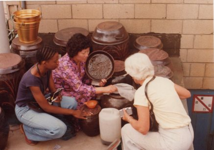 My grandma, right, peeks at some fermenting food, possibly kimchi.