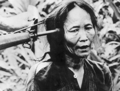 A Vietnamese civilian with a gun pointed at the side of her head. (Photo by Keystone