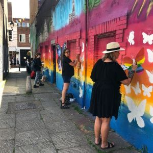 Artists painting butterflies on a mural in Brighton