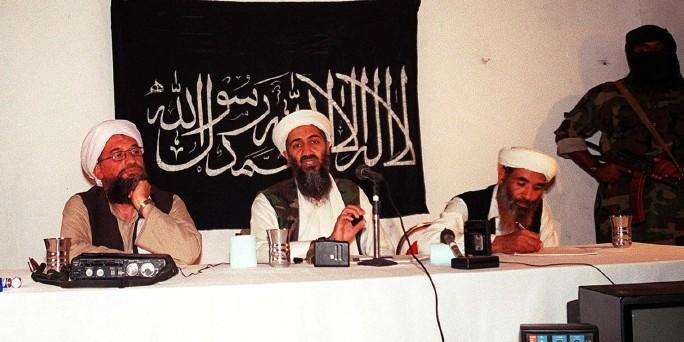 Osama bin Laden und Mitstreiter von Al Qaida vor schwarzer Fahne