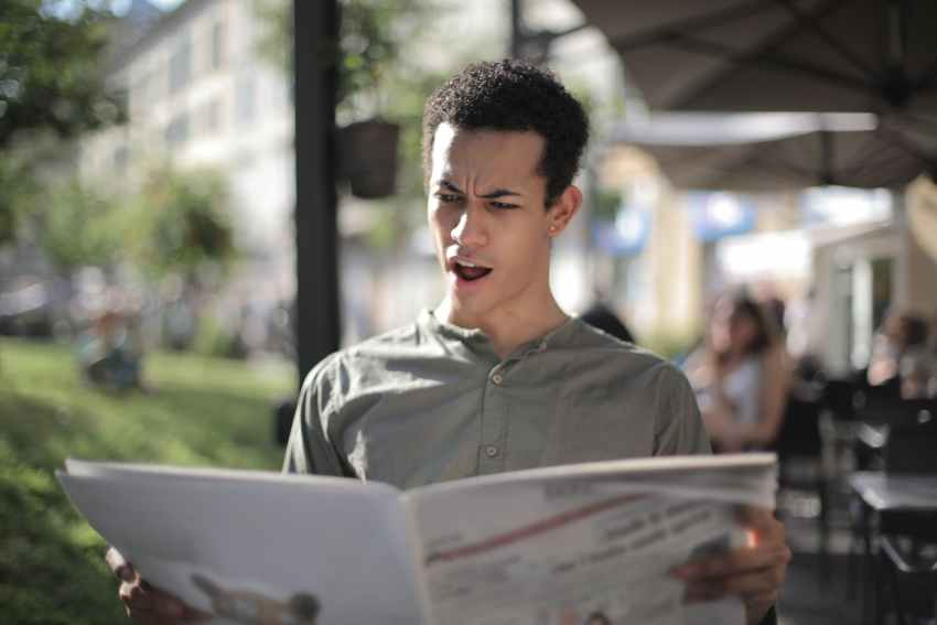 shallow focus photo of man reading newspaper
