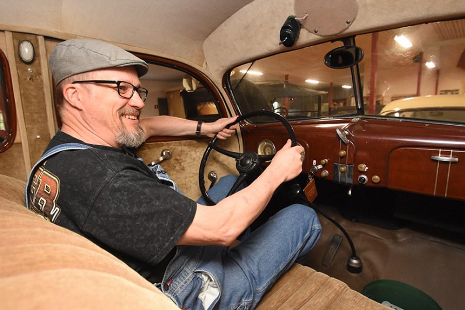 Jari Turunen istuu museon tiloissa 30-luvun jenkissä. Omassa tallissa on kolme vuoden 1961 Chrysleriä.