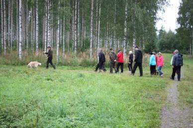 Maisema- ja kulttuurikävely Haapasalmella keräsi toistakymmentä osallistujaa. Joukkoa johdatti Markku Halonen koiransa kera. Kuva: Erkki Härkönen.