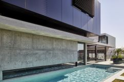 The-pool-runs-along-the-side-of-the-house-bounded-by-a-glass-wall