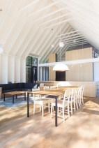 Window-on-the-Lake-cottage-features-a-high-ceiling-and-white-cedar-walls