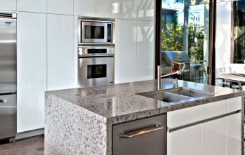 Built-in-kitchen-appliances-white-cabinets-and-granite-waterfall-countertop