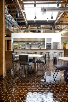 One-of-the-workspaces-is-a-casual-and-open-coffee-shop-cafeteria-style-space-with-a-high-ceiling-and-tiled-floor
