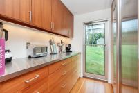 Adam-Kalkin-Shipping-Container-Home-galley-kitchen-with-stainless-steel-countertop
