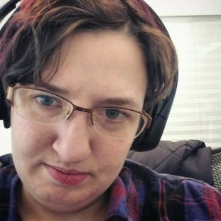 image is Kit, a white person with short brown hair tinged with reddish purple, wearing over the ear headphones and light brown glasses with no bottom rim.