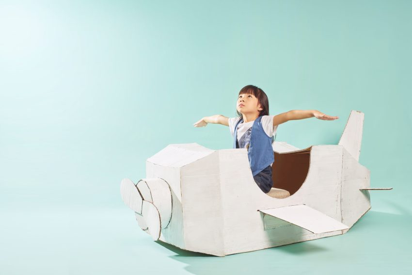 Child looking skyward from the cockpit of a white cardboard airplane