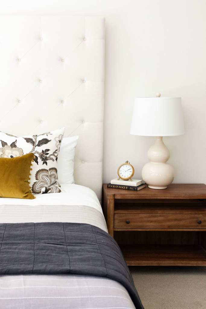guest bedroom with wood nightstand and linen bedding