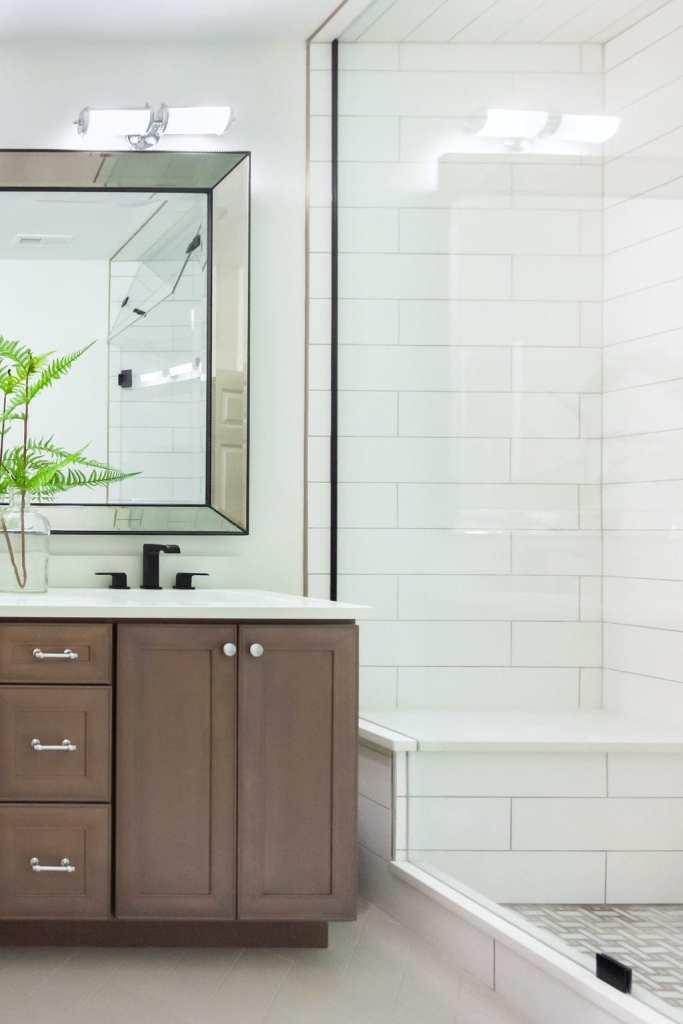Dark wood vanity and built-in shower bench