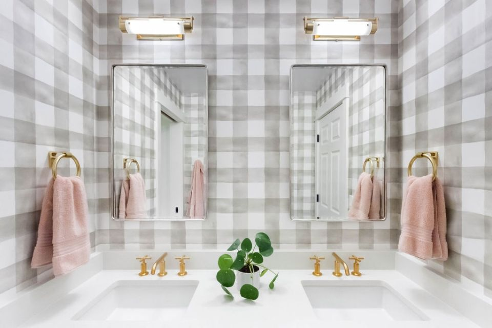 watercolor plaid wallpaper in bathroom with pink towels and gold hardware